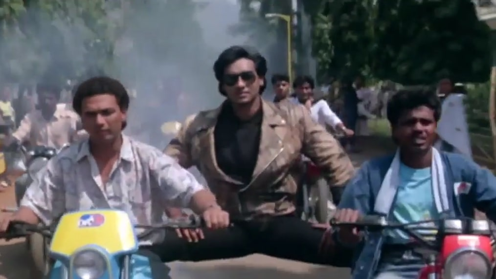 Ajay Devgn standing between two bikes stunt meme