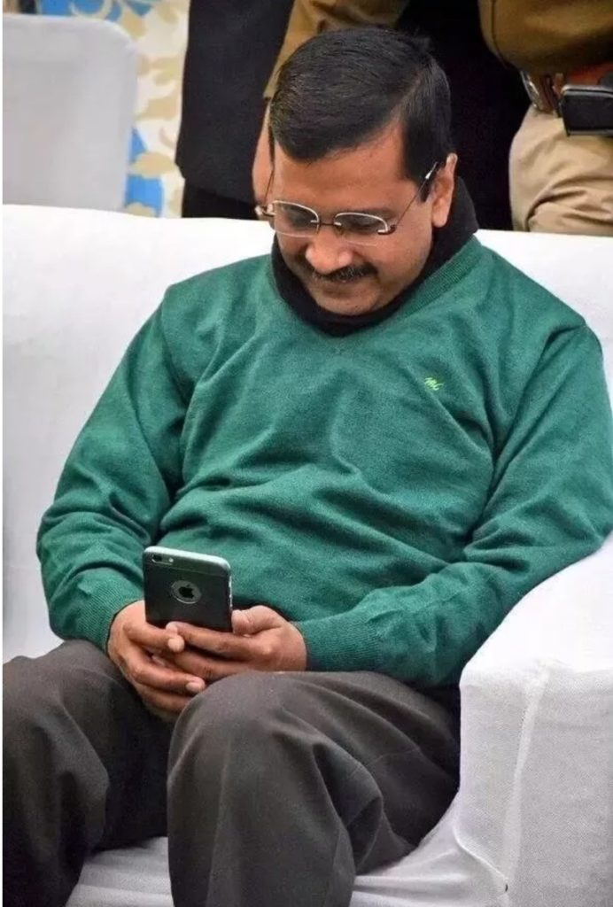 Arvind Kejriwal smiling looking at his mobile phone funny photo and meme