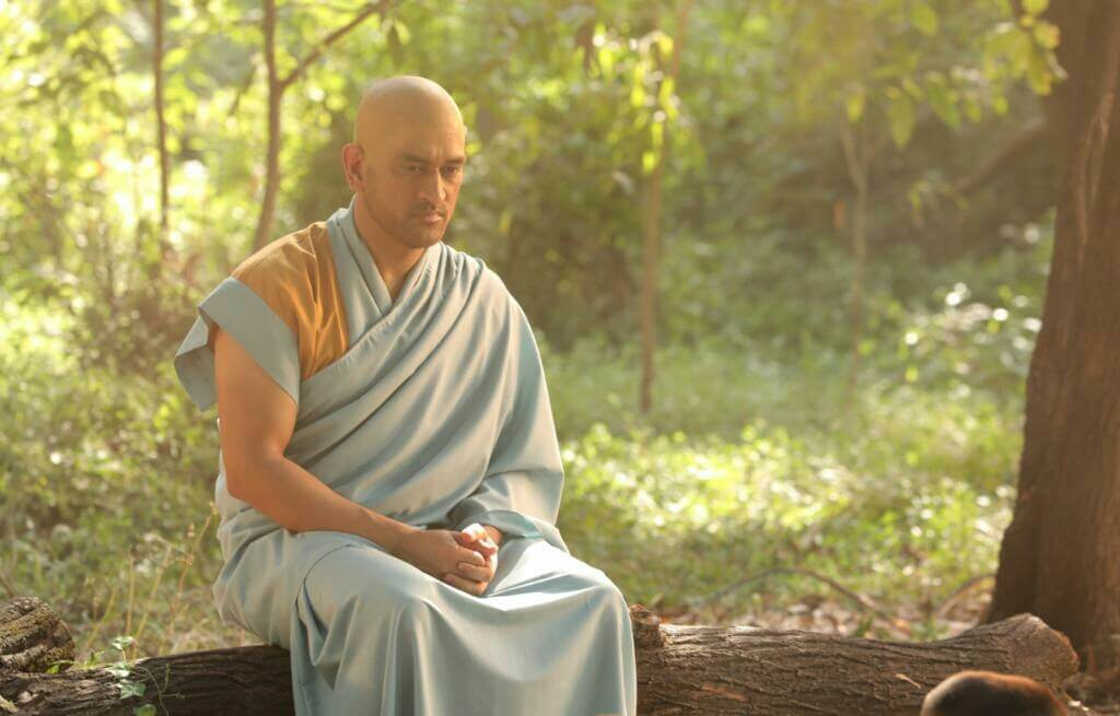 bald dhoni sitting in a monk's clothes