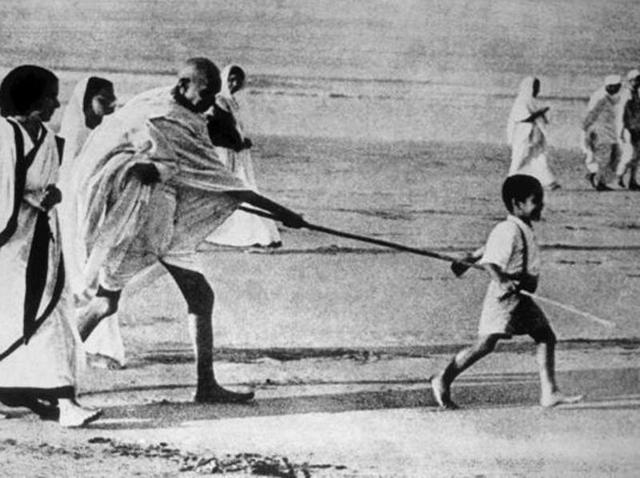 Boy Kanu Gandhi walking ahead of Mahatma holding one end of his stick in Dandi March