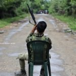 indian army personnel sitting on chair as he shows his weapon gun towards kashmiri protesters in Shopian