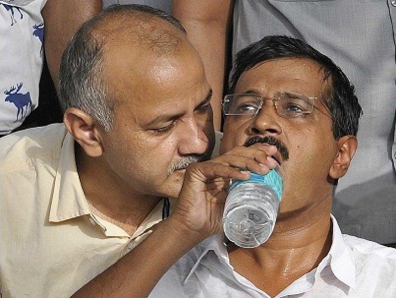 manish sisodia telling something to arvind kejriwal while drinking water