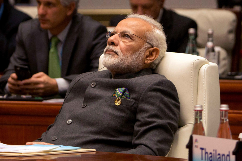 Narendra Modi leaning back resting and in deep thought on a arm chair photo